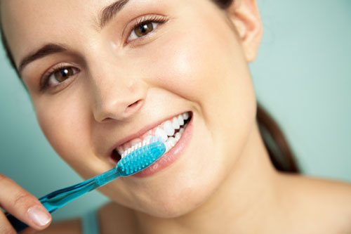 A woman brushing her teeth with a blue toothbrush.